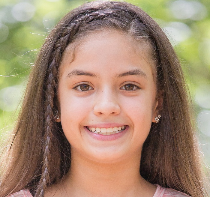 Preteen girl with clear aligners smiling