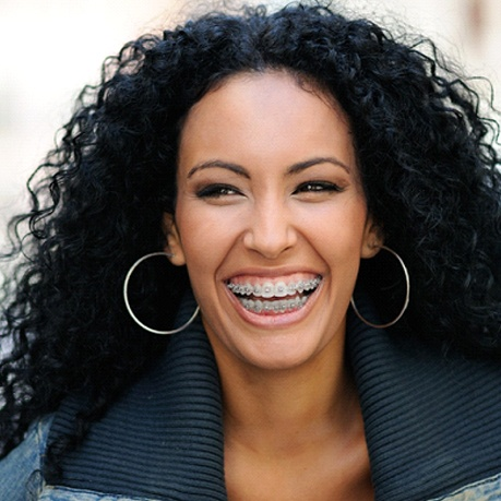A woman with long, dark, curly hair smiles while showing off her clear braces