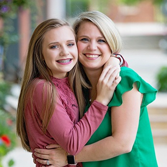 Mother giving teen daughter with braces a hug