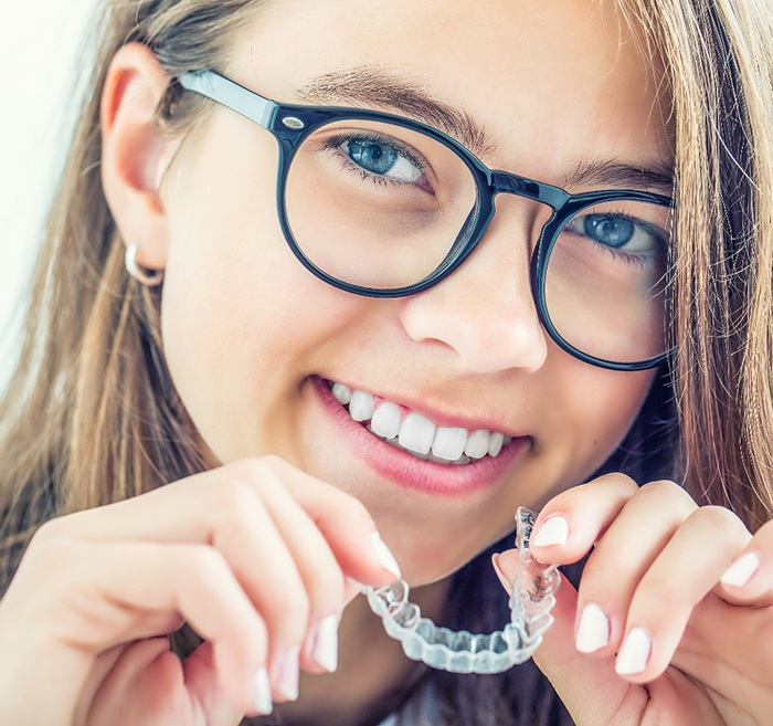 Teen girl smiling while holding Invisalign aligners