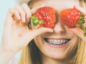 Smiling girl with braces holding strawberries follows tips from Cumming, GA orthodontist