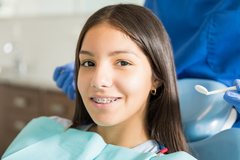 a young girl with braces smiling in preparation for seeing her orthodontist in Cumming, GA
