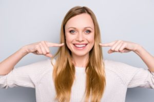 woman smiling and pointing at teeth