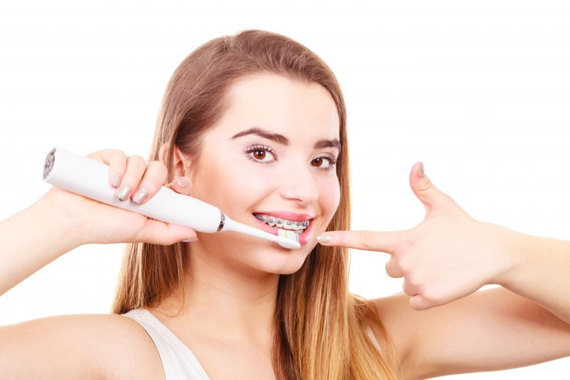 a young woman using an electric toothbrush to clean her teeth and braces in Cumming