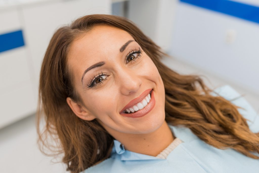 Woman with straight teeth smiling in orthodontist's treatment chair